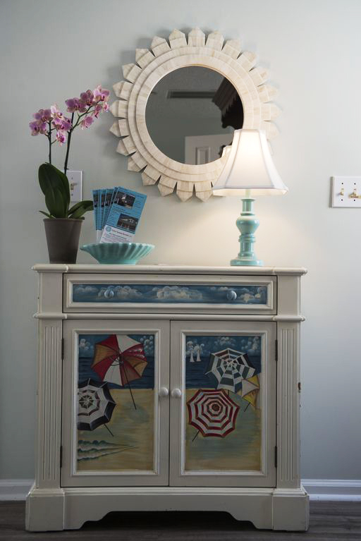 Entryway furniture with flowers, lamp and mirror