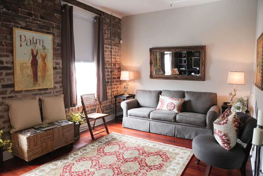 Savannah Loft living room with grey couch and mirror on wall.
