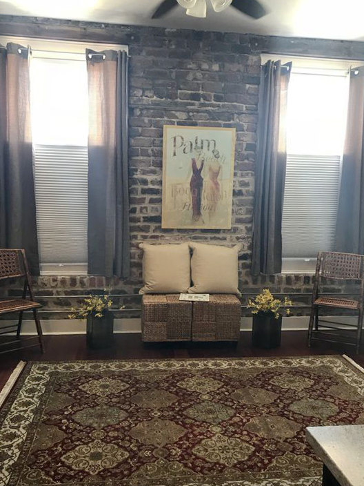 Savannah Loft living room with brick walls and decorative painting on wall.