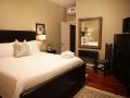 Savannah Loft bedroom showing entry door, mirror and bed.