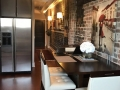A view of the Savannah Loft foyer from the  kitchen with refrigerator and table with white chairs. .